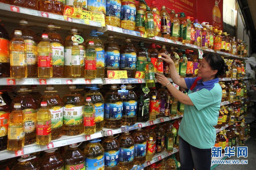 6月9日,售货员在河北省邯郸市复兴路某超市摆放待售的食用油.图片