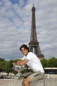 图文:纳达尔巴黎铁塔下展示奖杯 骑在墙墩上