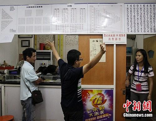 6月13日,一位彩民高举双手向投中奖注站的工作人员表示祝贺。中新社发 杨华峰 摄
