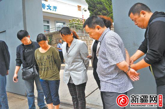 图为在昆明市公安局看守所门口,民警在给三名犯罪嫌疑人戴手铐.