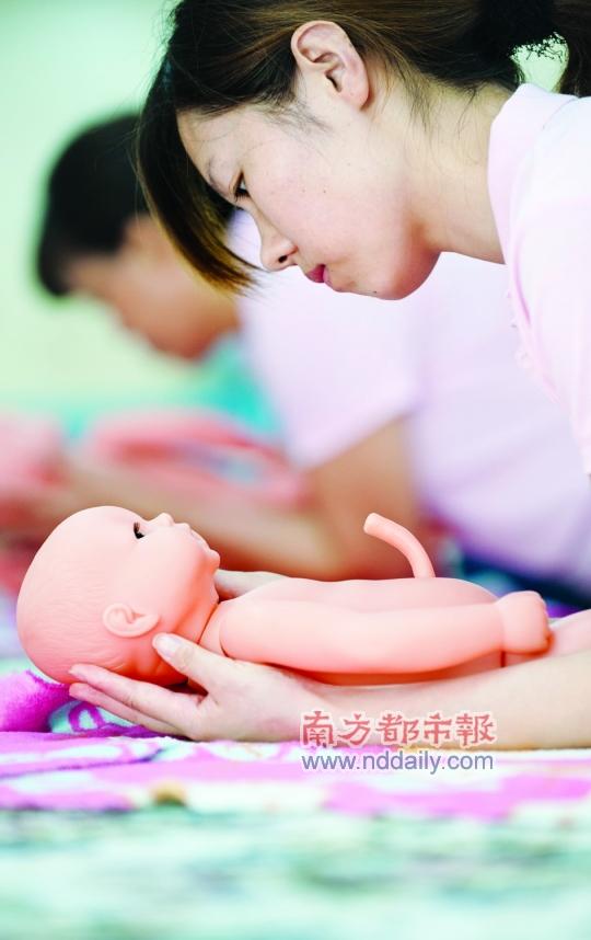 """娃娃轻握着学员玩具的""""小手"""",练习逗初生娃娃玩游戏.四个月婴儿干呕图片"""