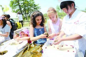 外国游客在妫水河畔体验包粽子,了解中国传统文化(北京日报 记者吴镝摄)