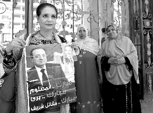 6月20日,在埃及开罗,一名埃及妇女手举穆巴拉克的照片在医院外守候。新华/法新