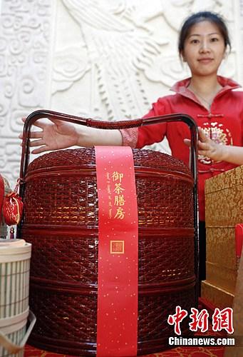 """6月20日,北京御茶膳房总店工作人员在展示""""天圆篮""""端午粽子礼篮。这款产品在其官方网站售价达1880元,并号称""""故宫督造""""。中新社发张浩 摄"""