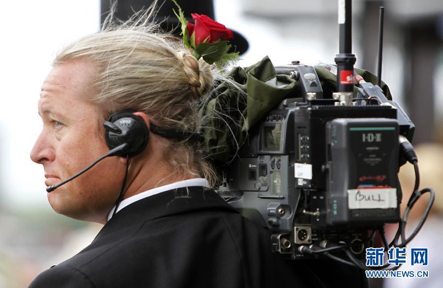 鲜花 阿斯科特/6月22日,一位头戴鲜花的摄像师在皇家阿斯科特赛马会上。