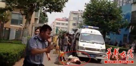 肇事女子将被撞小女孩从救护车上拖下来后,继续躺在救护车前阻扰救治。视频截图