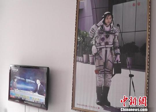 客厅墙壁上挂着刘洋出征太空的巨幅照片。