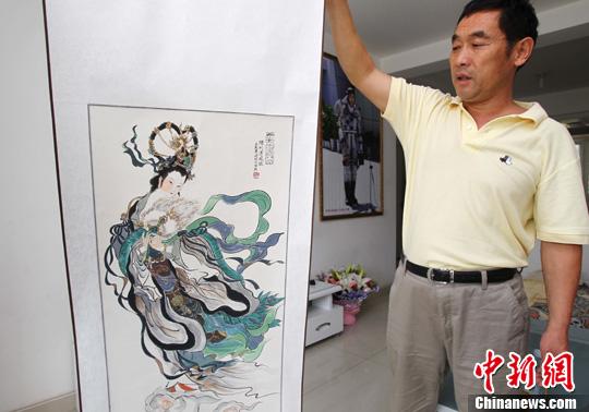 6月27日,在河南郑州女航天员刘洋父母家中,刘洋舅舅牛振西展示一幅《飞天图》,刘洋父母准备携《飞天图》迎接女儿凯旋。