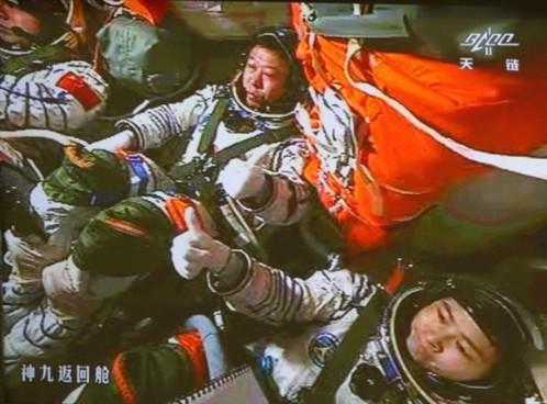 (神舟九号载人航天器与天宫一号手控对接成功。三位航天员举手庆贺。)(《证券时报》快讯中心)