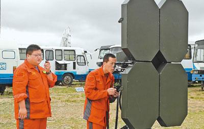 红格尔苏木测控现场,两名工作人员在调试高空监控设备。 本报记者 王君平摄