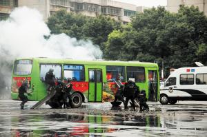 窗玻璃爆破后,突击队员利用钩镰枪、破窗梯等强攻装备迅速突进公交车。 颜家文摄