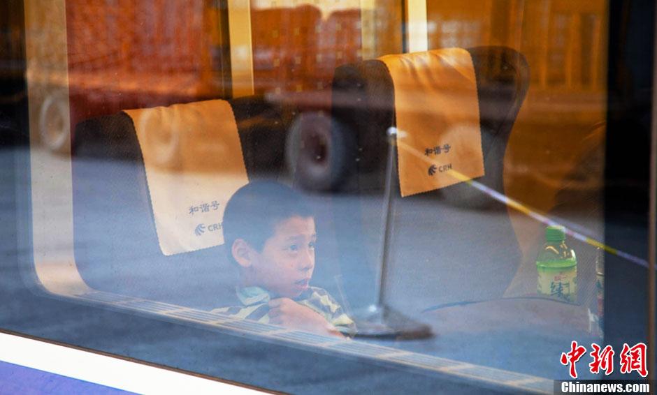 """随着中小学生纷纷放暑假,连日来,福州火车站掀起""""小候鸟""""返乡潮,许多在榕读书的外来务工人员子弟纷纷趁着暑假回老家乐享暑假。图为一名""""小候鸟""""车中静待列车启动。龙敏摄"""