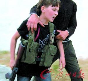 这位手中握枪的孩子面对小伙伴的死亡伤心不已。