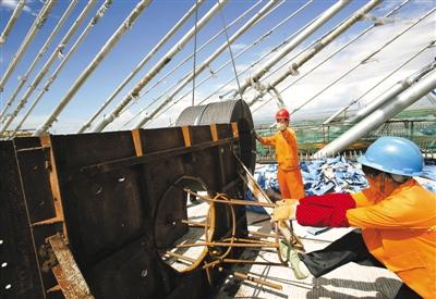 工人们正在桥上装卸钢筋。