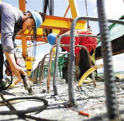 工人们正在桥面施工。