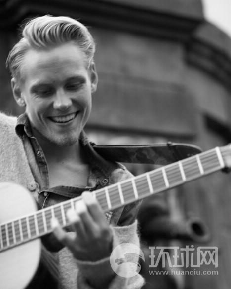 平静的冬天过后总会是热闹的夏天:一位街头艺人正在斯德哥尔摩街边演奏吉他。