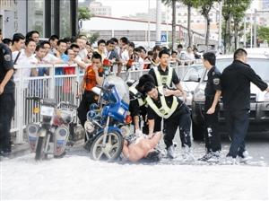 执法人员救下自焚男子并将其控制住。
