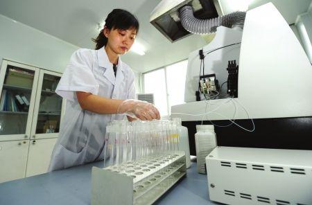 工作人员在电感耦合等离子质谱室使用仪器对水质进行化验,每种水样都进行了仔细编号。