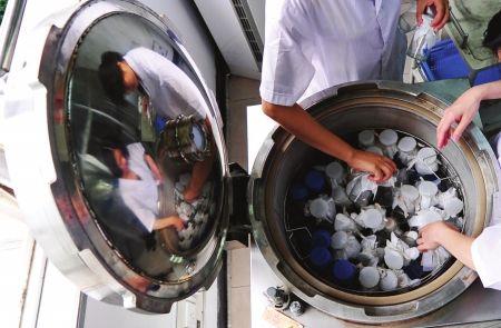 工作人员在微生物室对器皿进行高压消毒以确保化验准确。