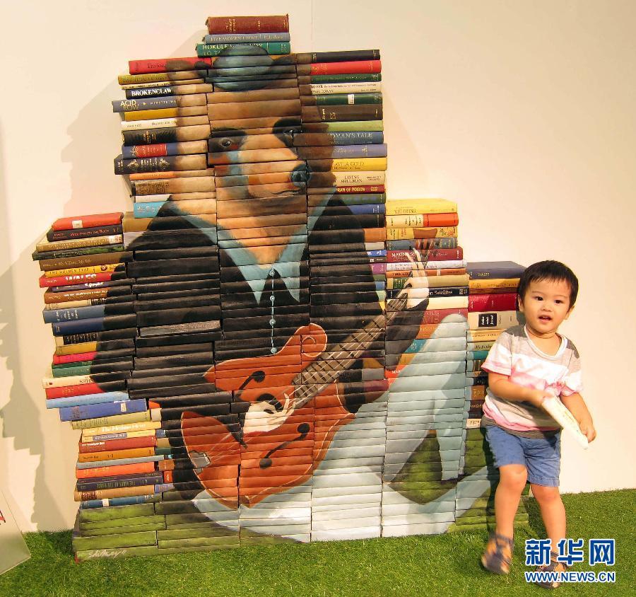 绘画作品 艺术 壁画 书脊/7月11日,一名小朋友在香港时代广场与书皮上的绘画作品合影。
