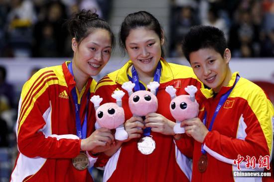 资料图:2011年11月18日,2011年女排世界杯在日本东京落下帷幕,上届冠军意大利卫冕成功,美国队获得亚军,中国队获得季军。图为中国队参加颁奖仪式。中新社发 富田 摄