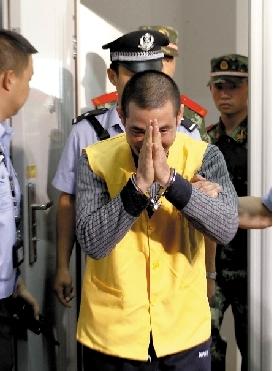 进入审讯室,糯康双手合十与老挝警方人员打招呼。