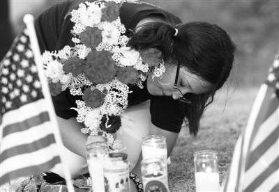 7月20日,在美国奥罗拉市,市民来到枪击案发现场附近为遇难者献上鲜花。新华社发