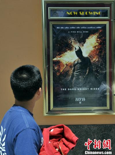当地时间7月21日,一名洛杉矶观众在影院前的《蝙蝠侠3:黑暗骑士崛起》广告画前留步注目。中新社发 毛建军 摄