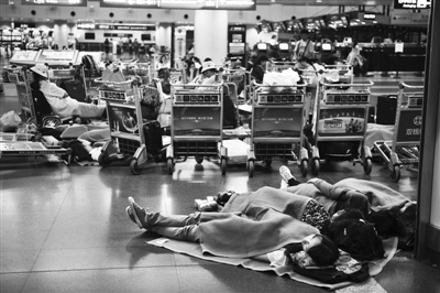 7月22日凌晨3点,首都机场T2航站楼滞留的旅客。新京报记者 李飞 摄