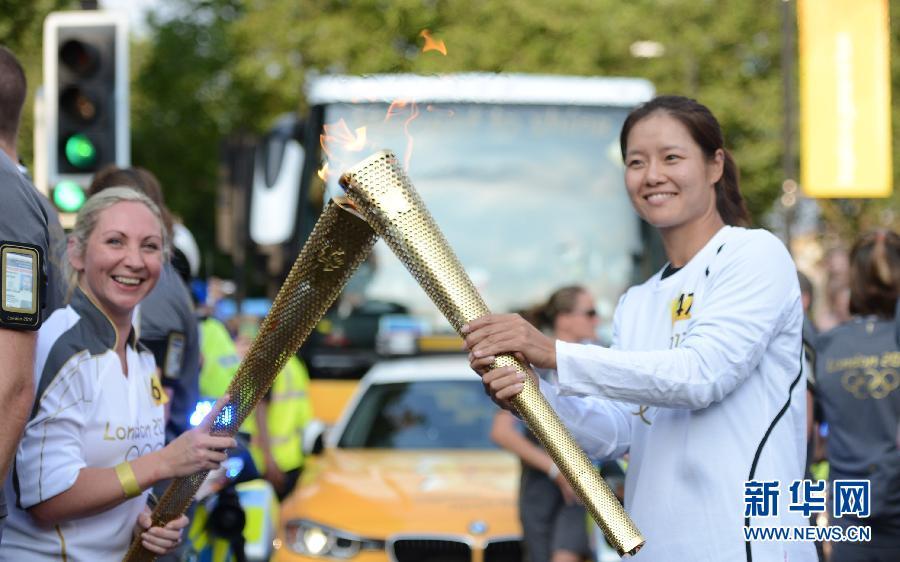 7月25日,中国网球运动员李娜在火炬传递中。当日,伦敦奥运会火炬继续在伦敦传递。 新华社记者吴晓凌摄