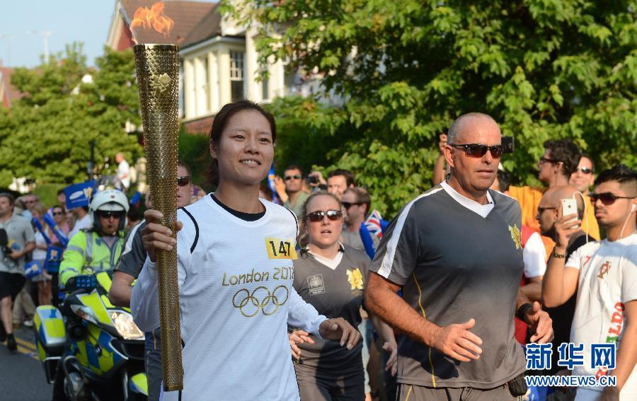 7月25日,中国网球运动员李娜(右)在火炬传递中。当日,伦敦奥运会火炬继续在伦敦传递。新华社记者吴晓凌摄