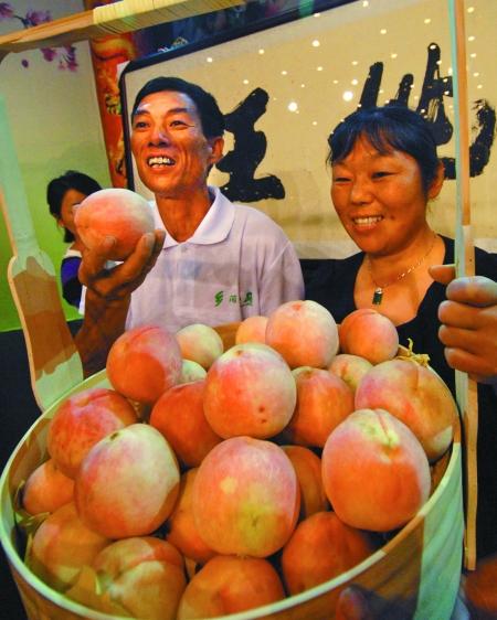 """新科""""桃王""""溪口镇湖山村的桃农孙永虎夫妇向大家介绍他们家的水蜜桃。记者张峰摄"""