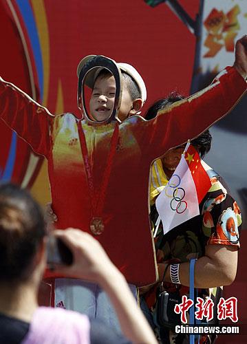 7月26日,在上海欢乐谷,一名儿童在家长的帮助下体验奥运夺冠激情一刻。随着伦敦奥运会开幕的临近,上海市民的奥运热情也随之高涨。中新社发 汤彦俊 摄