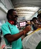 图文:上海申花抵达广州 德罗巴在队旗上签名