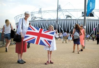 """伦敦当地时间7月25日晚,伦敦奥运会开幕式第二次彩排在主体育场""""伦敦碗""""进行,约6万名观众提前目睹盛典。图为前来观看彩排的祖孙两人在""""伦敦碗""""前留影"""