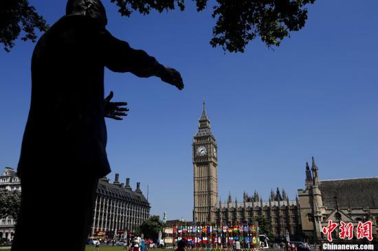 """当地时间7月26日,在伦敦著名景点大本钟旁的绿地上,新建的国旗墙吸引市民和""""奥运游客""""。记者 富田 摄"""