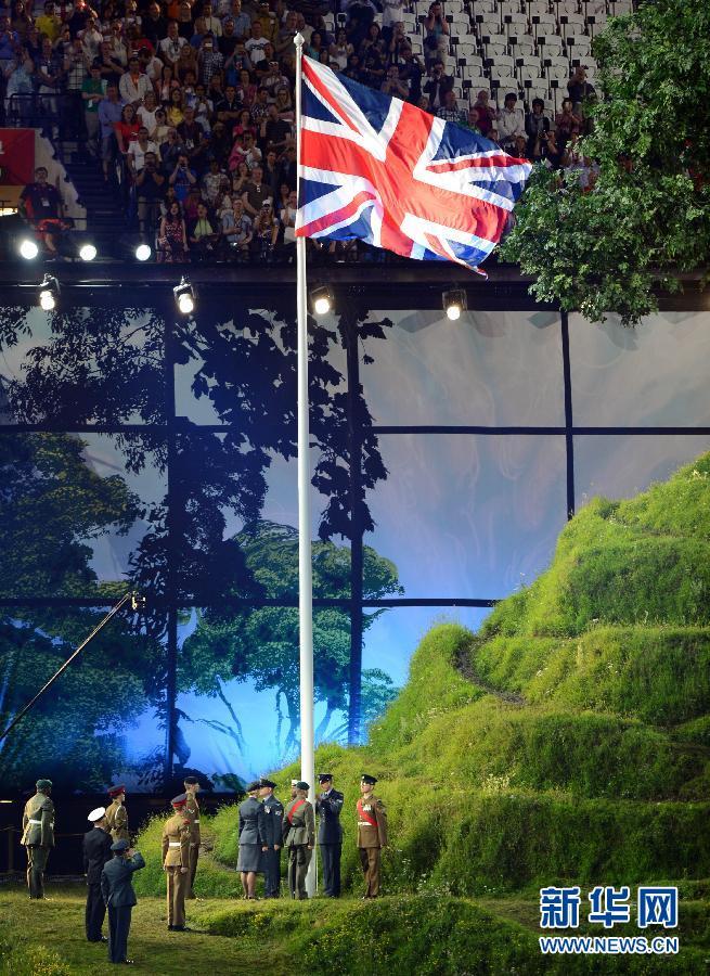 """7月27日,第三十届夏季奥林匹克运动会开幕式在伦敦奥林匹克公园主体育场""""伦敦碗""""举行。这是开幕式上,旗手执英国国旗入场。新华社记者杨磊摄"""