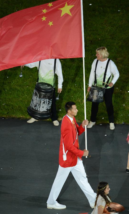 """7月27日,第三十届夏季奥林匹克运动会开幕式在伦敦奥林匹克公园主体育场""""伦敦碗""""举行。这是中国代表团旗手易建联(左前)执旗入场。中国代表团第42个入场,篮球运动员易建联担任旗手。"""