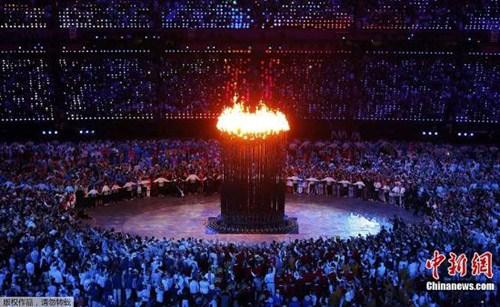 当地时间2012年7月27日,伦敦奥运会开幕。在开幕式尾声,7名年轻的火炬手聚集在场地中央,点燃会场中央铜质花瓣上的小火炬,小火炬依次燃起,最终合成一个大的奥林匹克主火炬。