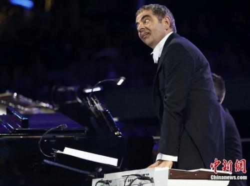 """当地时间7月27日,2012年伦敦奥运会,开幕式隆重举行。图为""""憨豆先生""""与乐队同台表演。"""