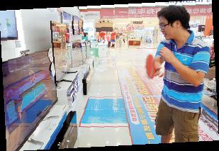 """图为一位顾客在和电视机里的""""奥运冠军""""进行乒乓对战。本报记者 徐冰摄"""