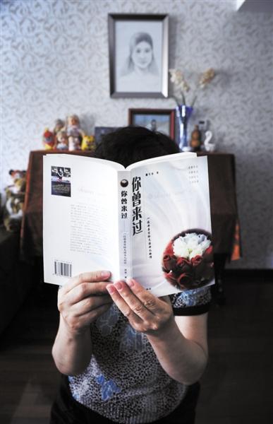 一名失独母亲,举着她写给女儿的书《你曾来过》,背后是女儿的钢琴和画像。