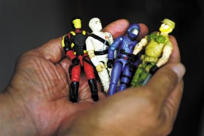 一名失独父亲,满是皱纹的手里,捧着儿子小时候玩的玩具。
