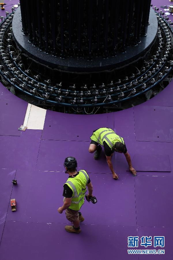 """7月30日,奥运主火炬已经从""""伦敦碗""""的中央区域移到该体育场的南入口处。为7月30日,两名工作人员(下)在熊熊燃烧的主火炬旁走过。新华社记者李明摄"""