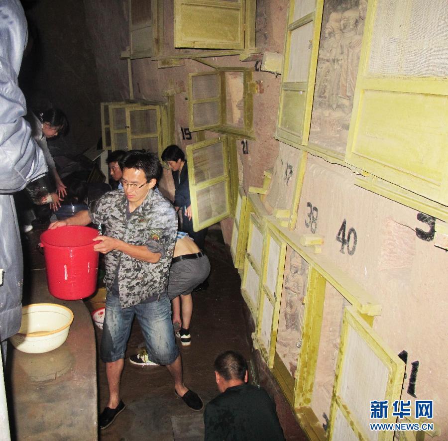 7月30日凌晨,甘肃省炳灵寺文物保护研究所工作人员在清理炳...