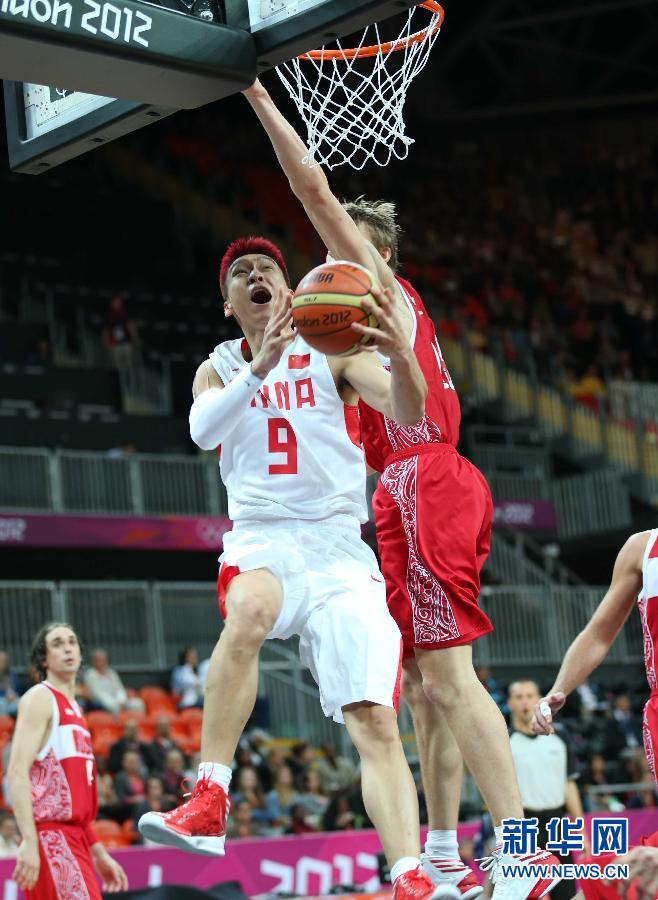7月31日,中国队球员王治郅(右)在比赛中进攻。