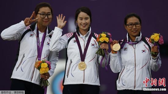 7月29日,伦敦,2012伦敦奥运会次日射箭女团决赛,中国队射箭女团仅仅一环落后于韩国屈居亚军。图为韩国队登上领奖台。