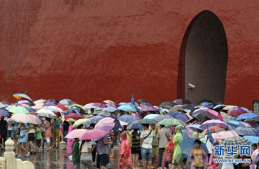 北京/7月31日,一名小游客在北京故宫保和殿广场的积水处玩耍。