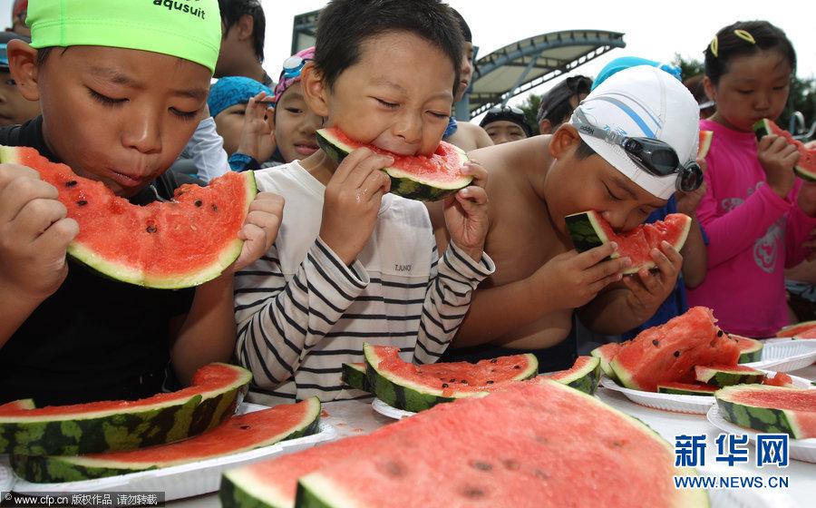 参加活动的小朋友们在大口大口地吃西瓜时无意中做出的可爱表情成为
