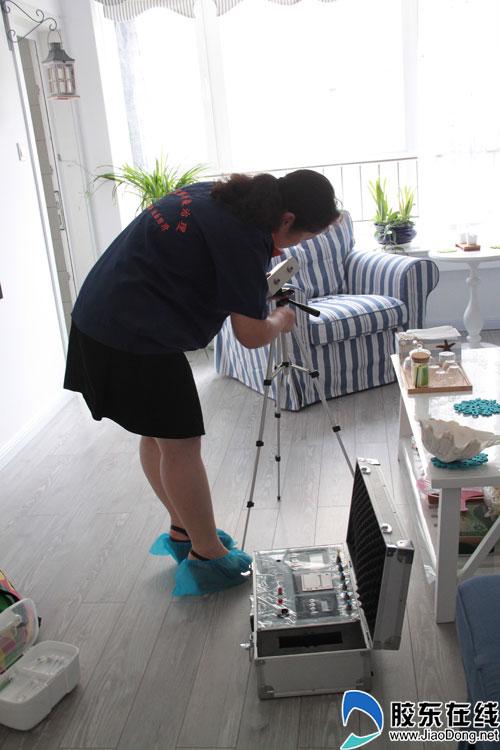 工作人员在客厅架设检测仪器
